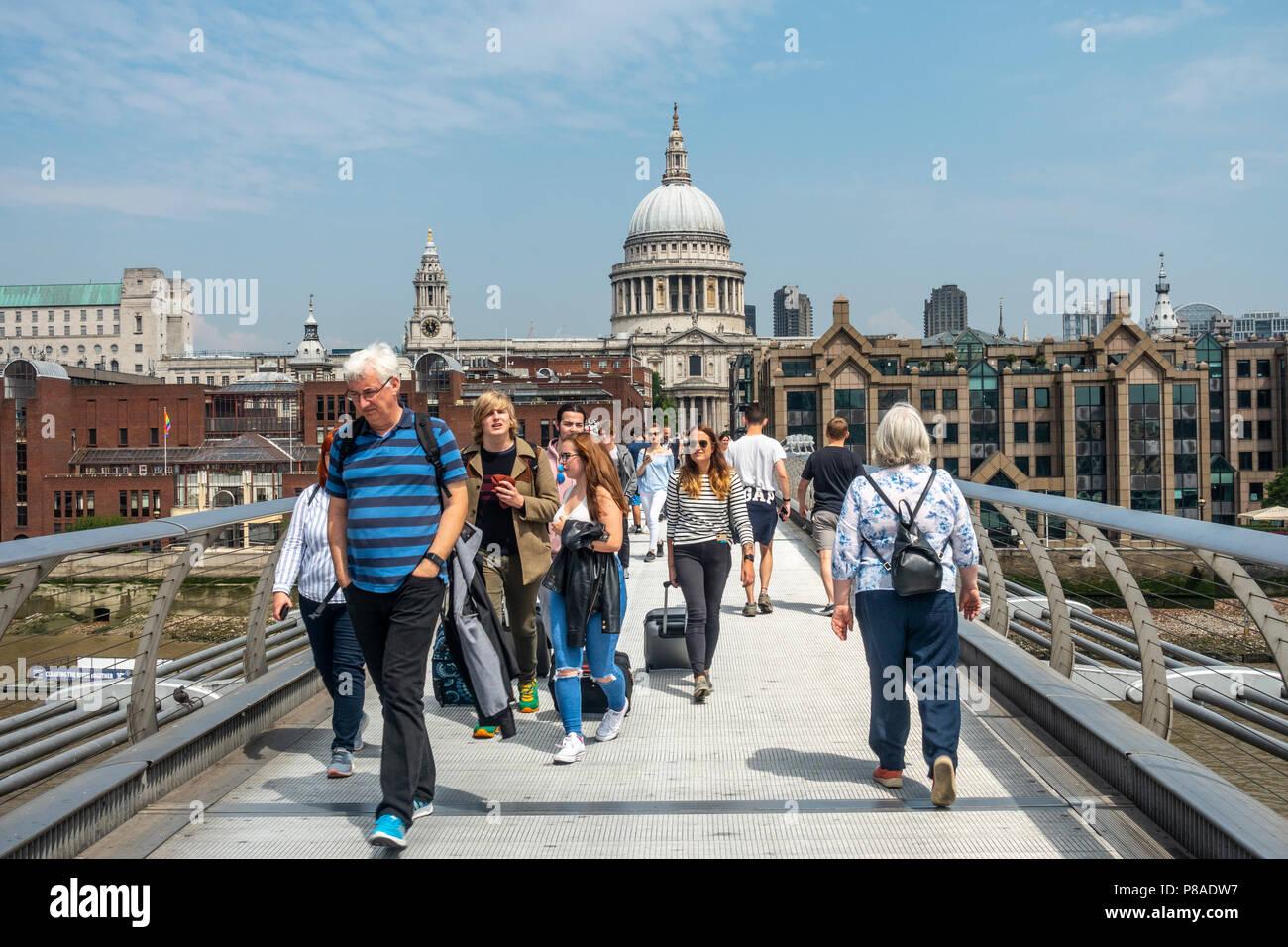 Passengers crossing the London Millennium Footbridge / Millennium Bridge over the River Thames towards St Paul's Cathedral in central London, England - Stock Image