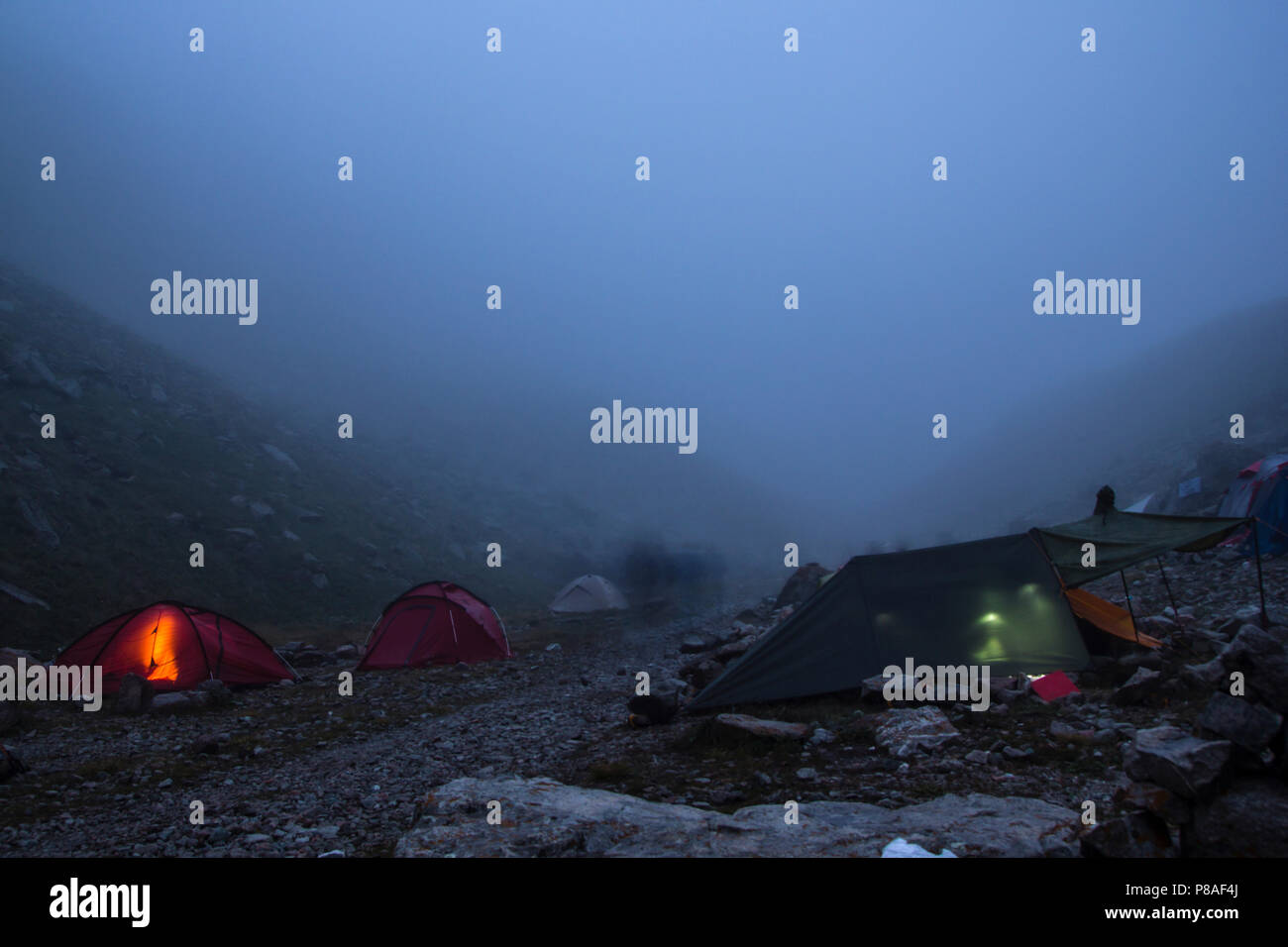 camping with tents and tourists in mountain valley at night and fog, Russian Federation, Caucasus - Stock Image