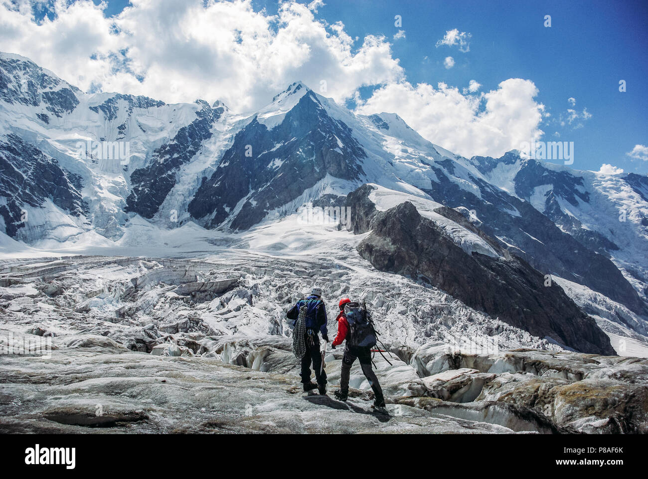 male travelers hiking in snowy mountains, Russian Federation, Caucasus, July 2012 - Stock Image