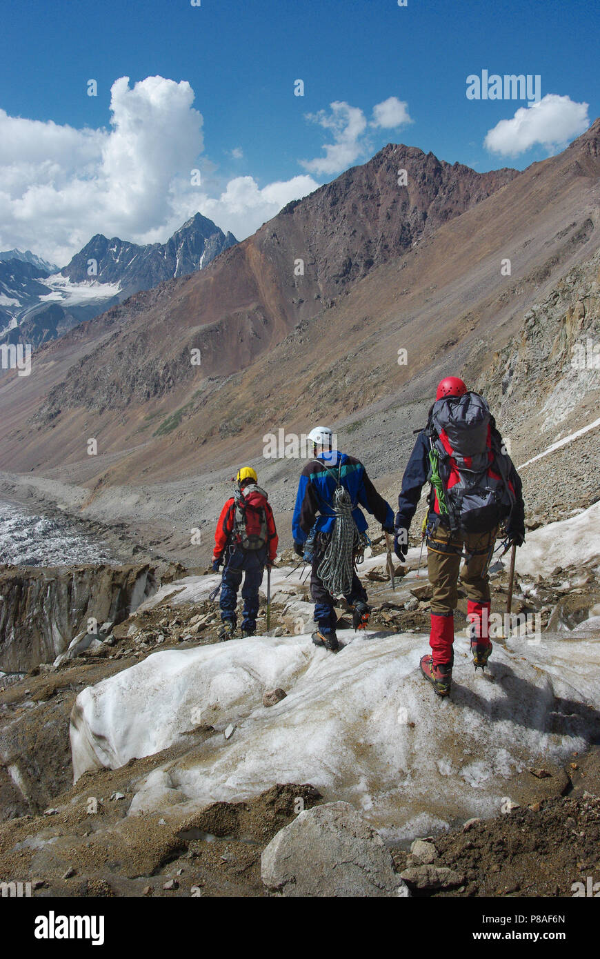 travelers hiking in snowy mountains, Russian Federation, Caucasus, July 2012 - Stock Image