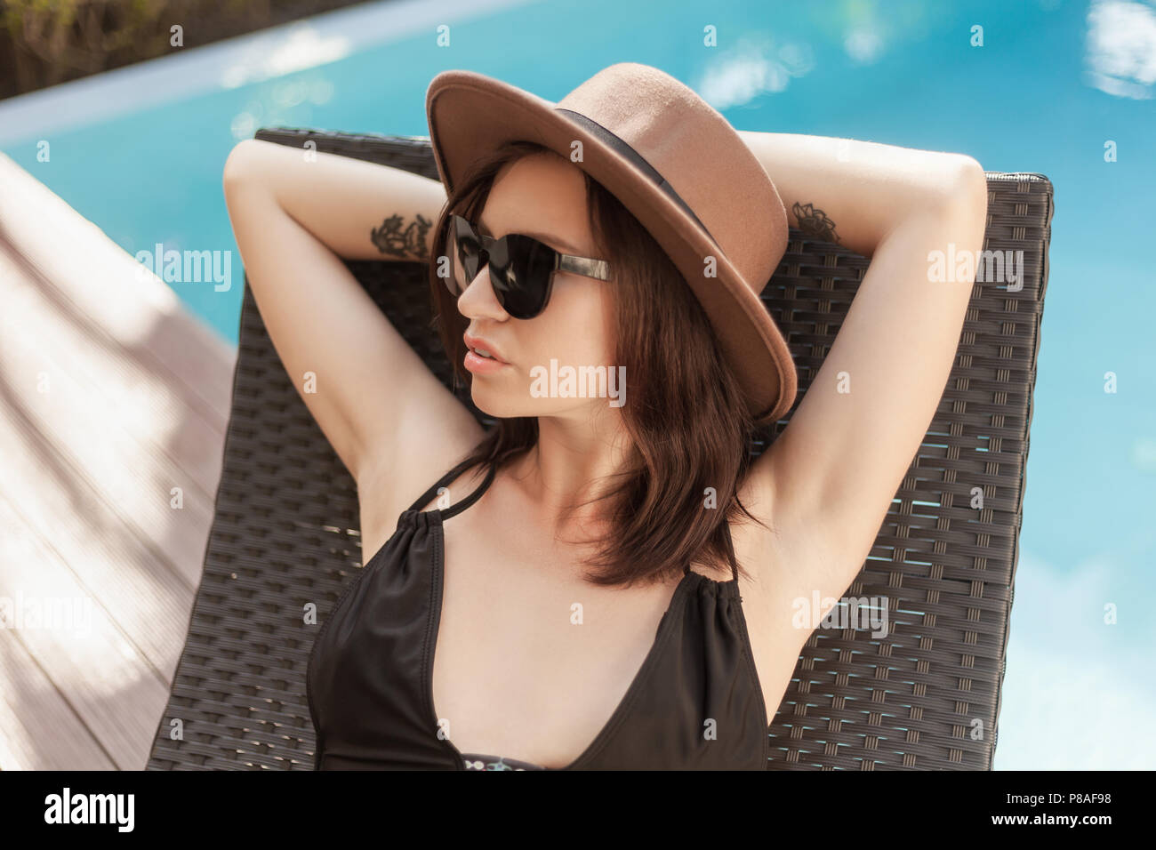 young woman in bikini and hat relaxing in sun lounge at poolside - Stock Image