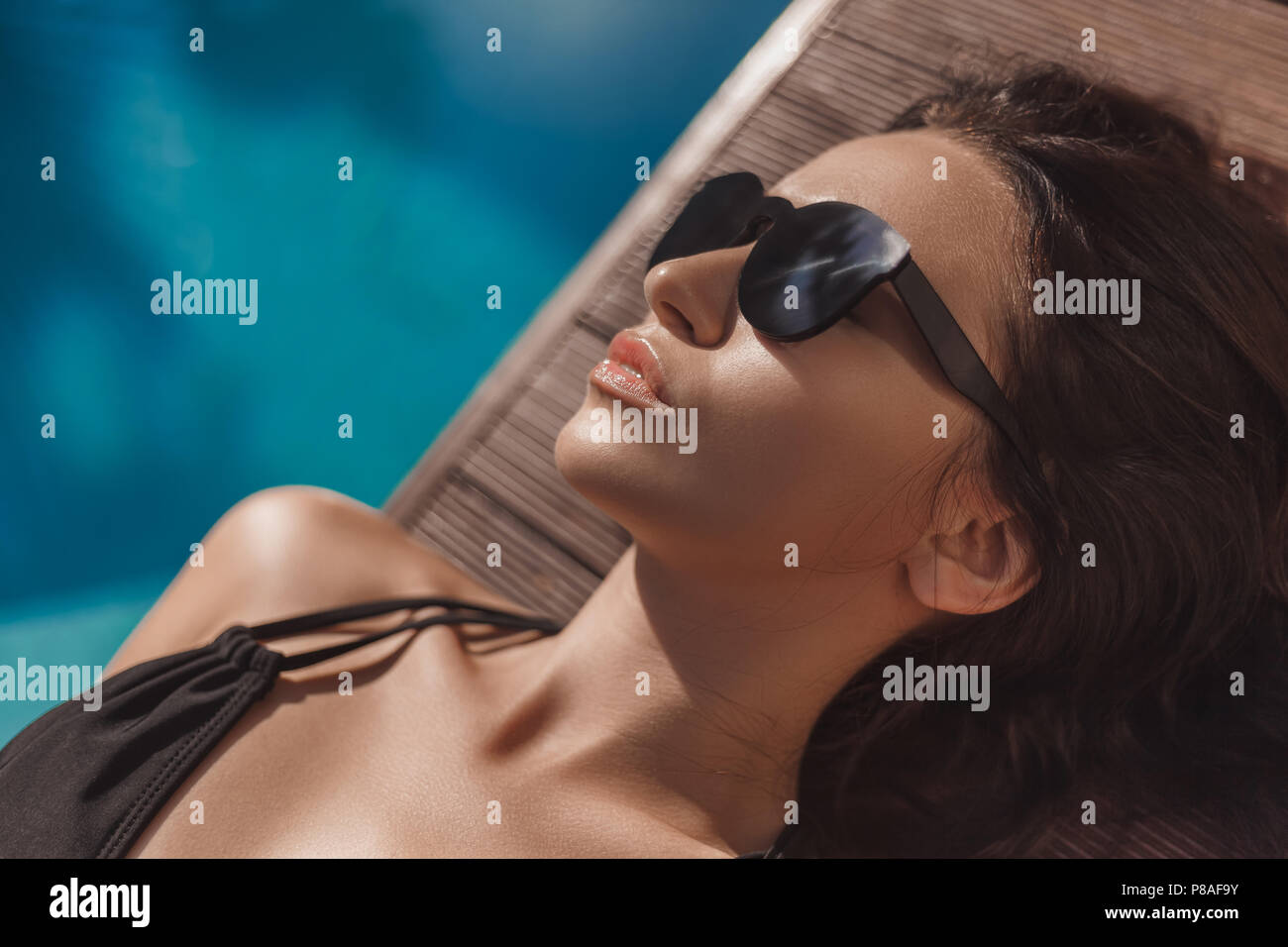 close-up portrait of young woman in black bikini lying at poolside - Stock Image