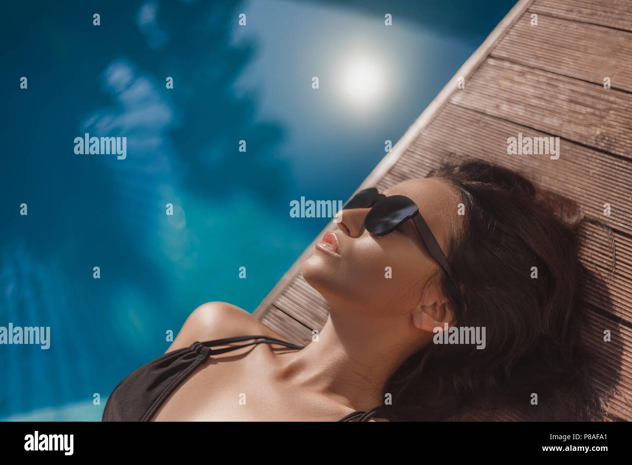 close-up portrait of relaxed young woman in black bikini lying at poolside - Stock Image