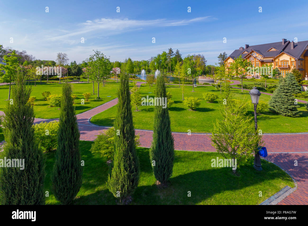 a huge lawn in front of a wooden mansion with stone paths, a green lawn, pyramidal thuja, deciduous trees, a pond with fountains under a blue cloudles Stock Photo