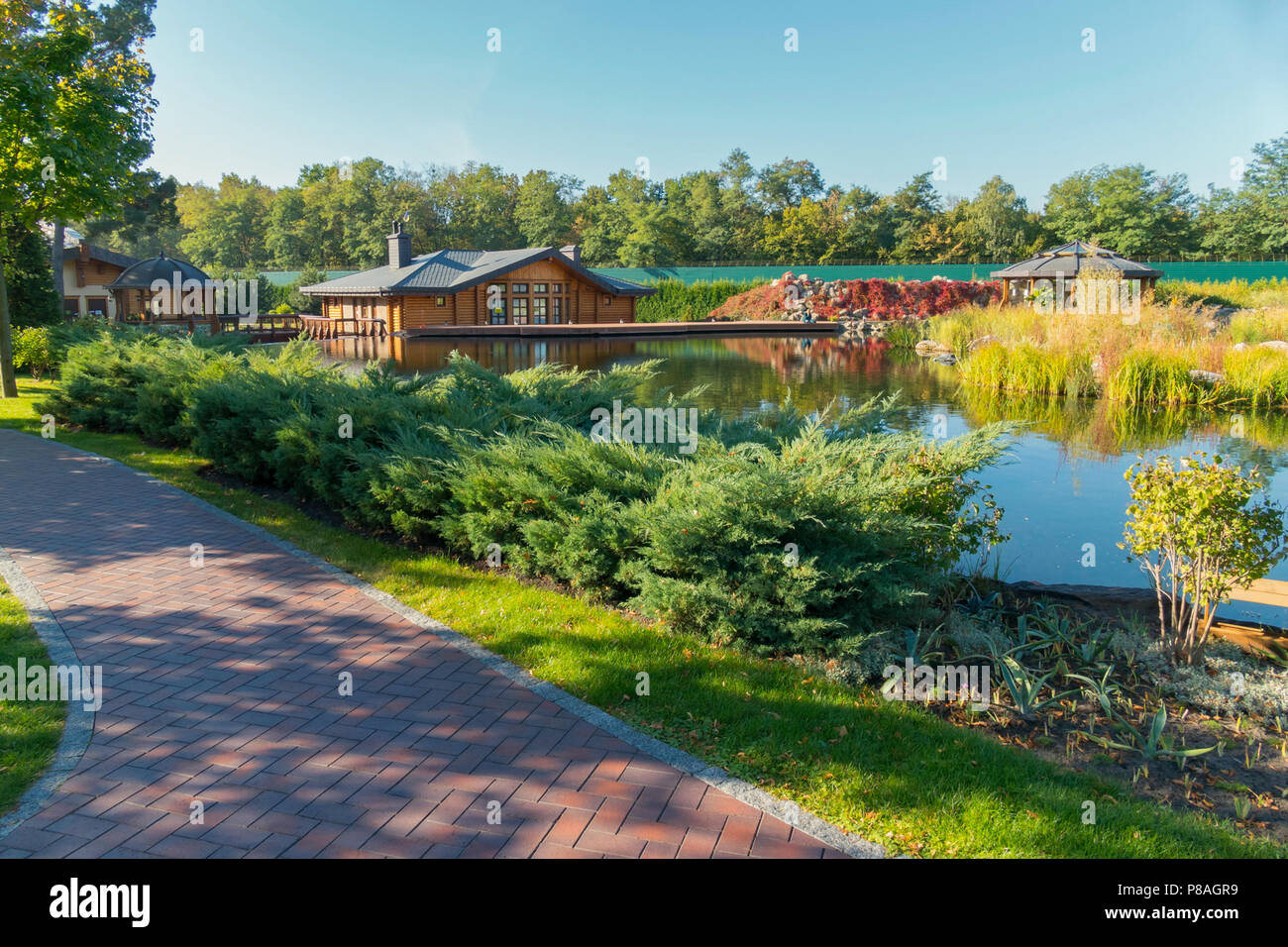 Several wooden houses and other buildings on the shore of a small pond . For your design Stock Photo