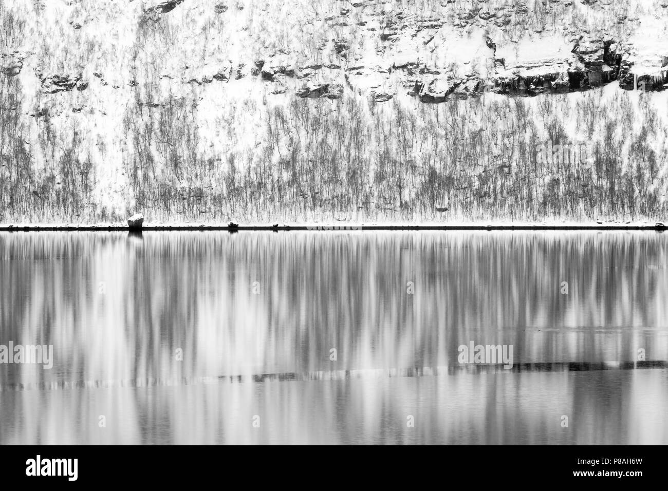 Abstract of snowcovered mountain in Arctic bay during winter, with reflection in water, Balsfjord, Norway - Stock Image