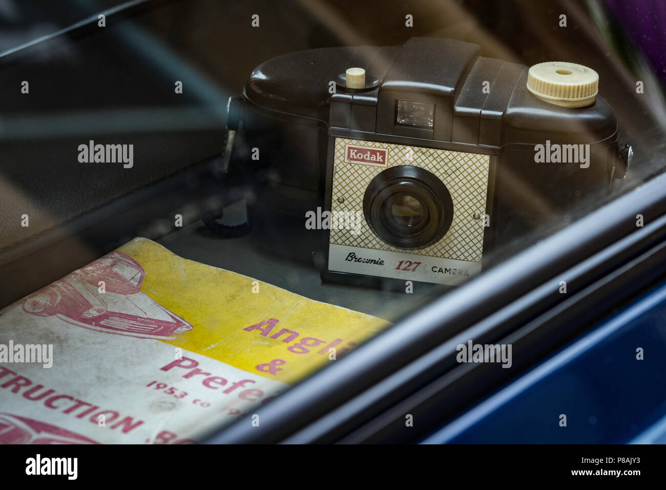 Kodak 127 Brownie camera on parcel shelf of classic Ford Anglia. - Stock Image