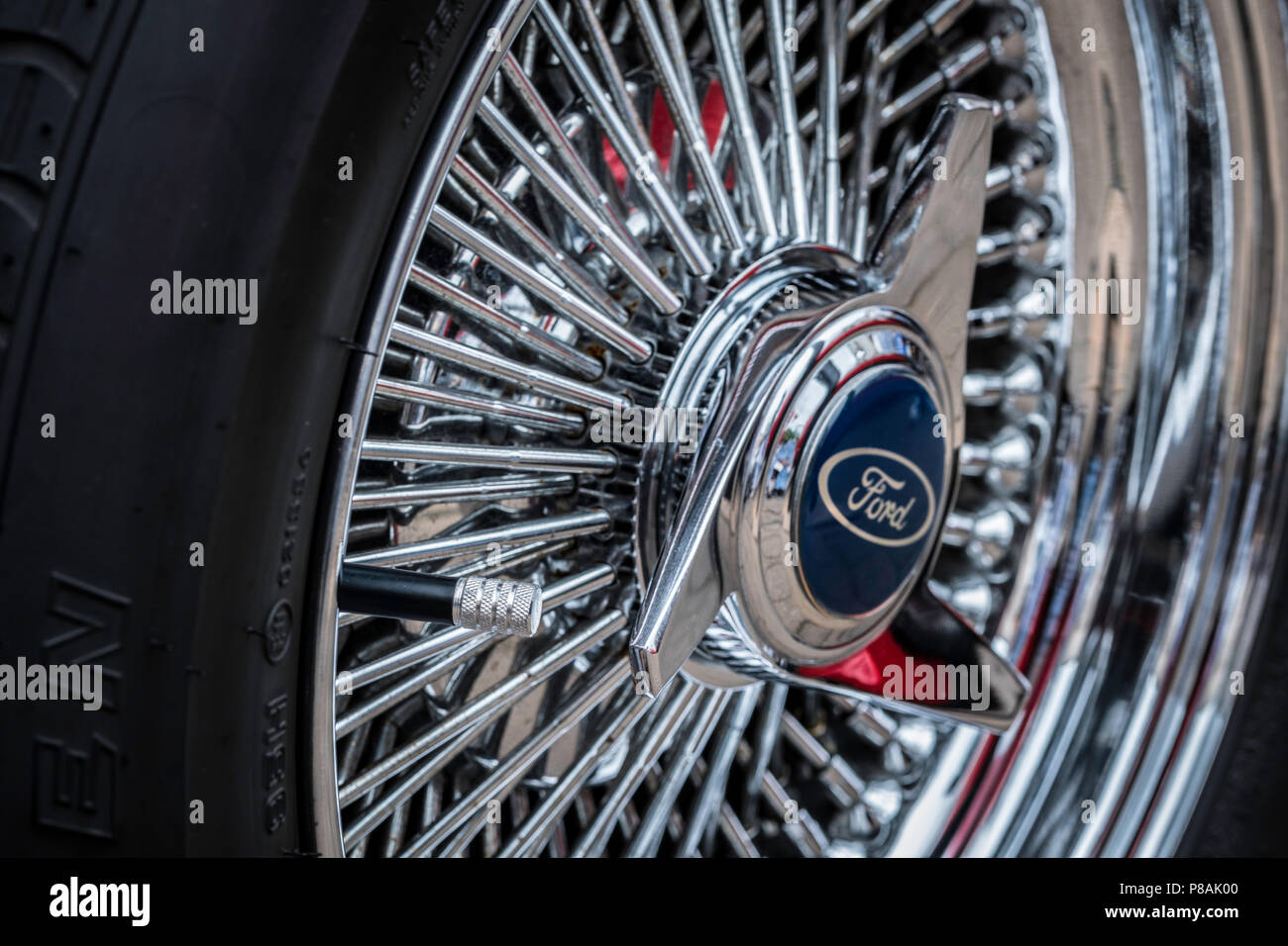 Chrome wire wheel with spinner and valve. - Stock Image