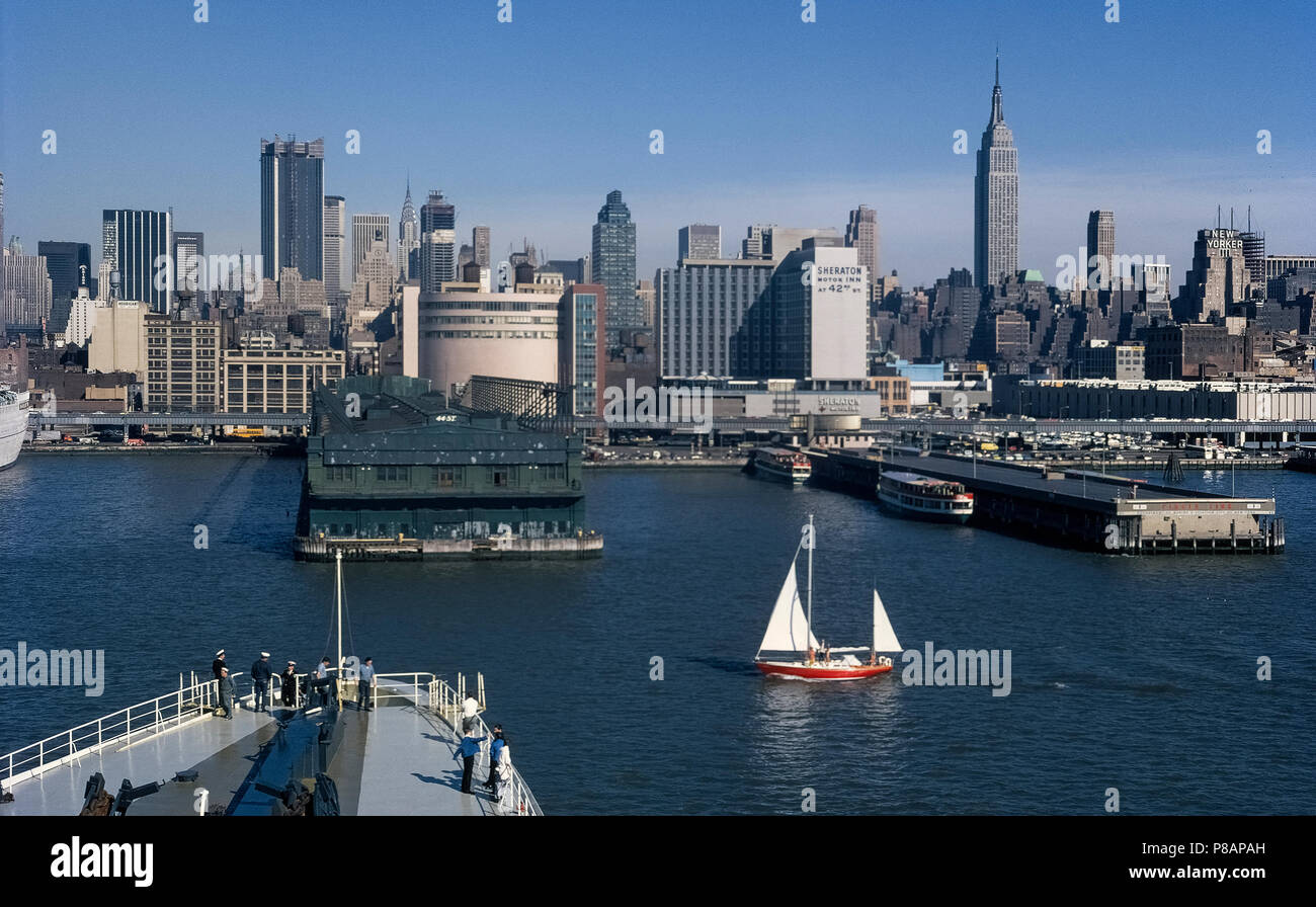 The skyline of New York City in New York, USA, as seen in 1971 looking from the Hudson River past ship piers and the elevated West Side Highway (12th Avenue) to buildings in Midtown Manhattan, including the towering Empire State Building to the right. This waterfront area has changed greatly in appearance with the 21st-Century establishment of the Hudson River Park that features pedestrian and bicycle paths connecting recreational facilities for many leisure and sports activities. Historical photograph. Copyrighted by Michele & Tom Grimm. - Stock Image