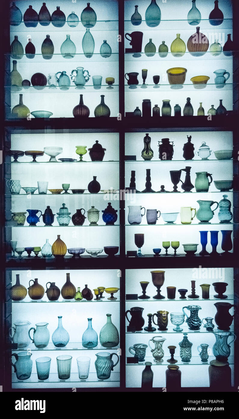 Antique glassware of many designs, shapes, sizes and colors is seen in 1966 in a backlighted display case at the Corning Glass Works in Corning, New York, USA. The glass company, now renamed Corning, Inc., established its Corning Museum of Glass in 1951 to educate visitors about the art, history and science of glass. Today the much-expanded museum boasts more than 45,000 glass objects, which is considered to be one of the best glass collections in the world. Historical photograph. - Stock Image