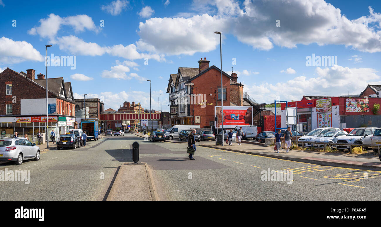 A typical scene along Winwick street, Warrington, Cheshire showing the Victorian Iron railway bridge in the distance adjacent to the Central Railway St - Stock Image