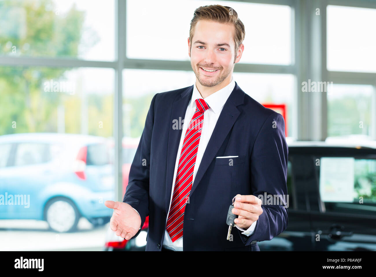 Young man or auto dealer in car dealership - Stock Image