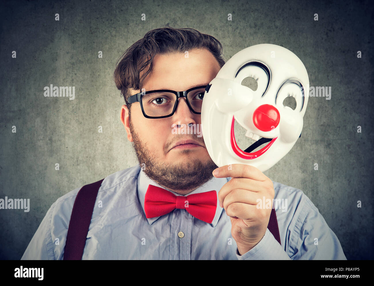 Young bearded man holding happy mask being sad and gloomy while looking at camera on gray background - Stock Image
