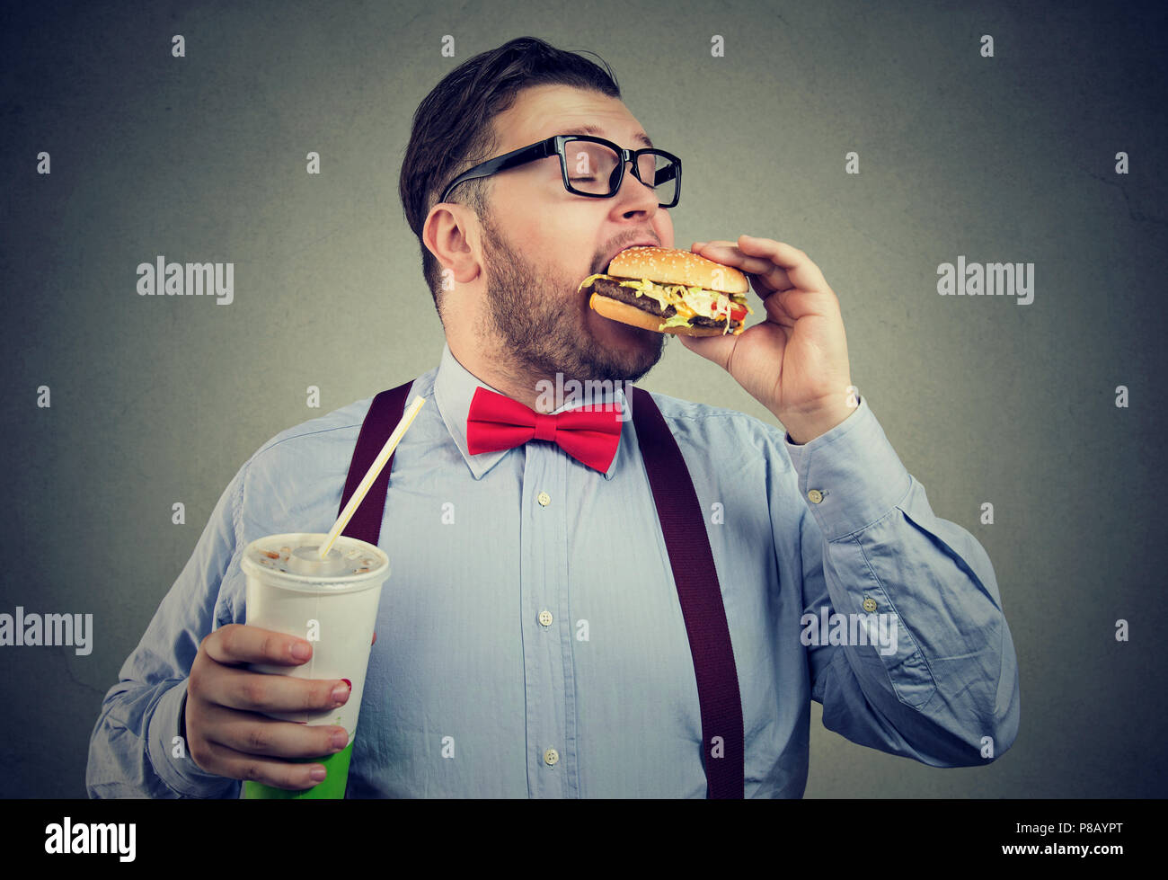 Overweight business man eating with appetite a burger holding a big can of soda drink - Stock Image