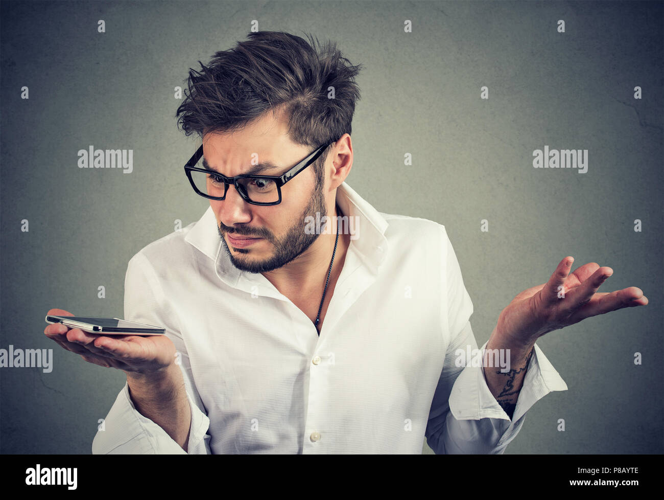 Young trendy man holding phone and looking at it with frustration having problems with gadget - Stock Image