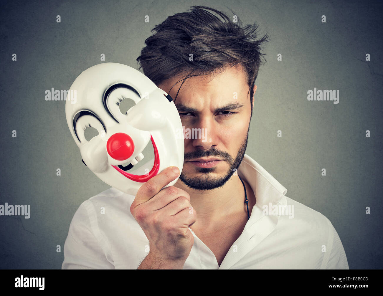 Young bearded man holding happy mask and feeling sad and gloomy while looking at camera on gray background - Stock Image