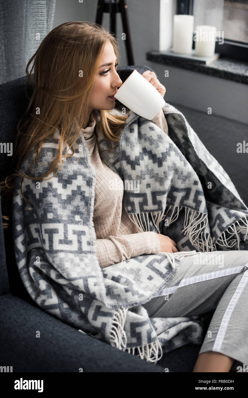 attractive young woman drinking coffee in comfy armchair with wool plaid - Stock Image