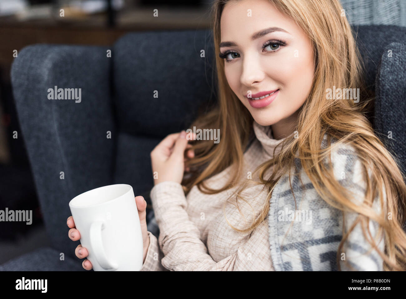 beautiful young woman sitting in comfy armchair with cup of coffee - Stock Image
