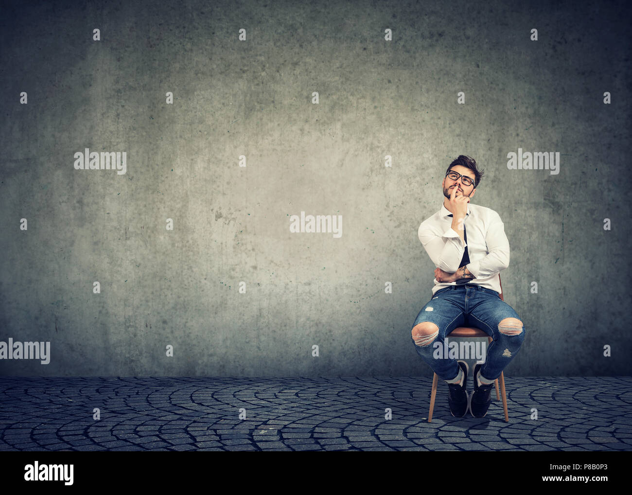 Young casual man sitting on chair and touching lips while looking up and thinking about new business ideas and career on gray background - Stock Image