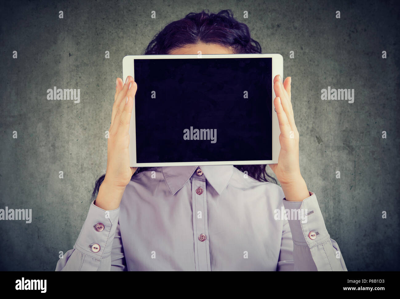 Anonymous brunette woman in shirt holding tablet in front of her face being incognito in social media on gray background - Stock Image