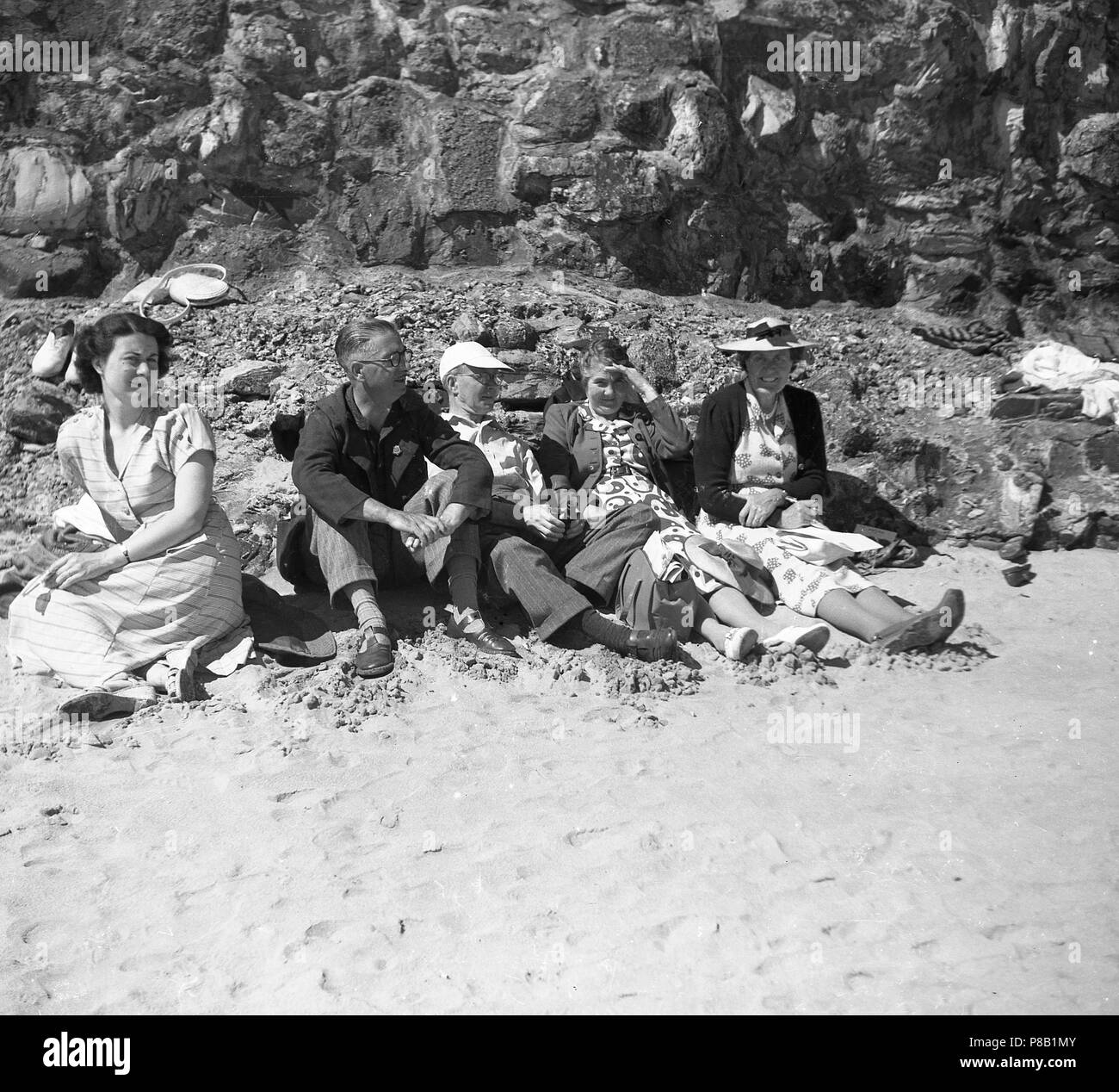 1950s, a hot day and a traditional British family in their day clothes sit together on a sandy beach .....and not a swim or bathingsuit in sight! Stock Photo