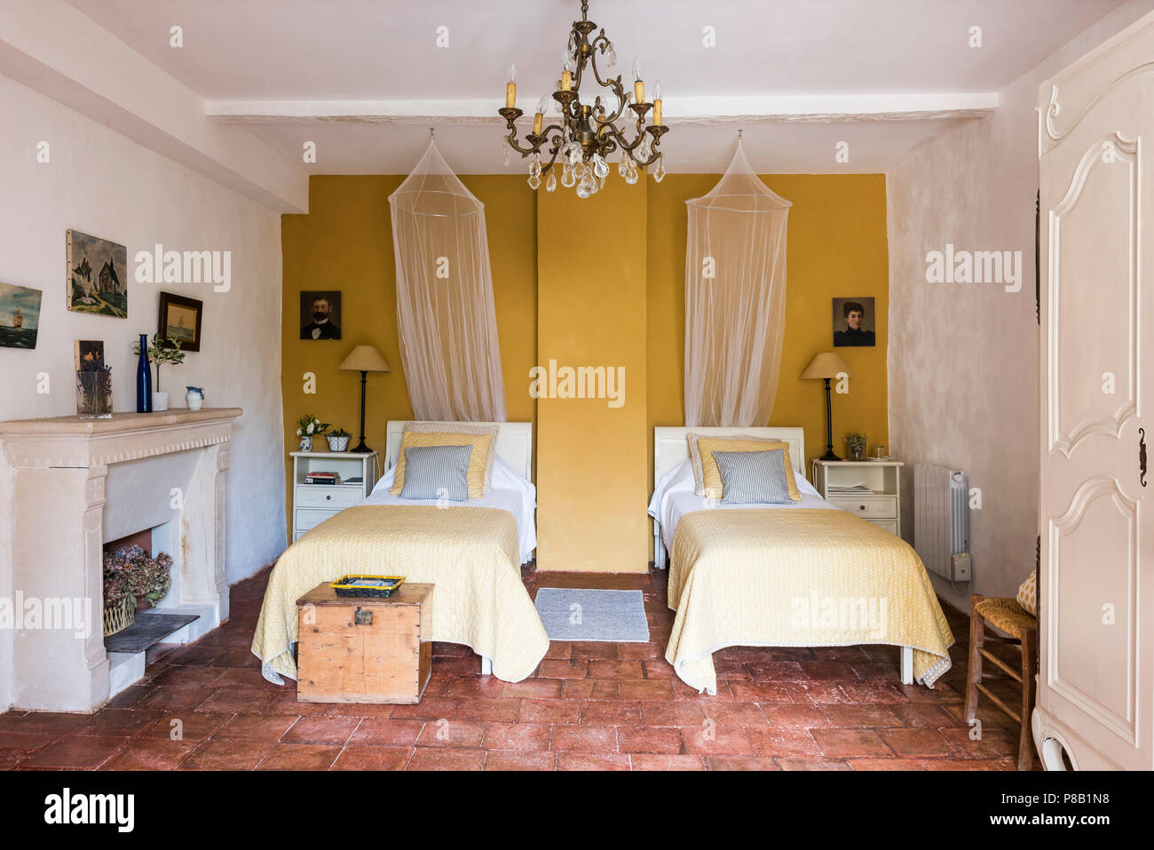 Yellow twin room with 18th century original teracotta tiles - Stock Image
