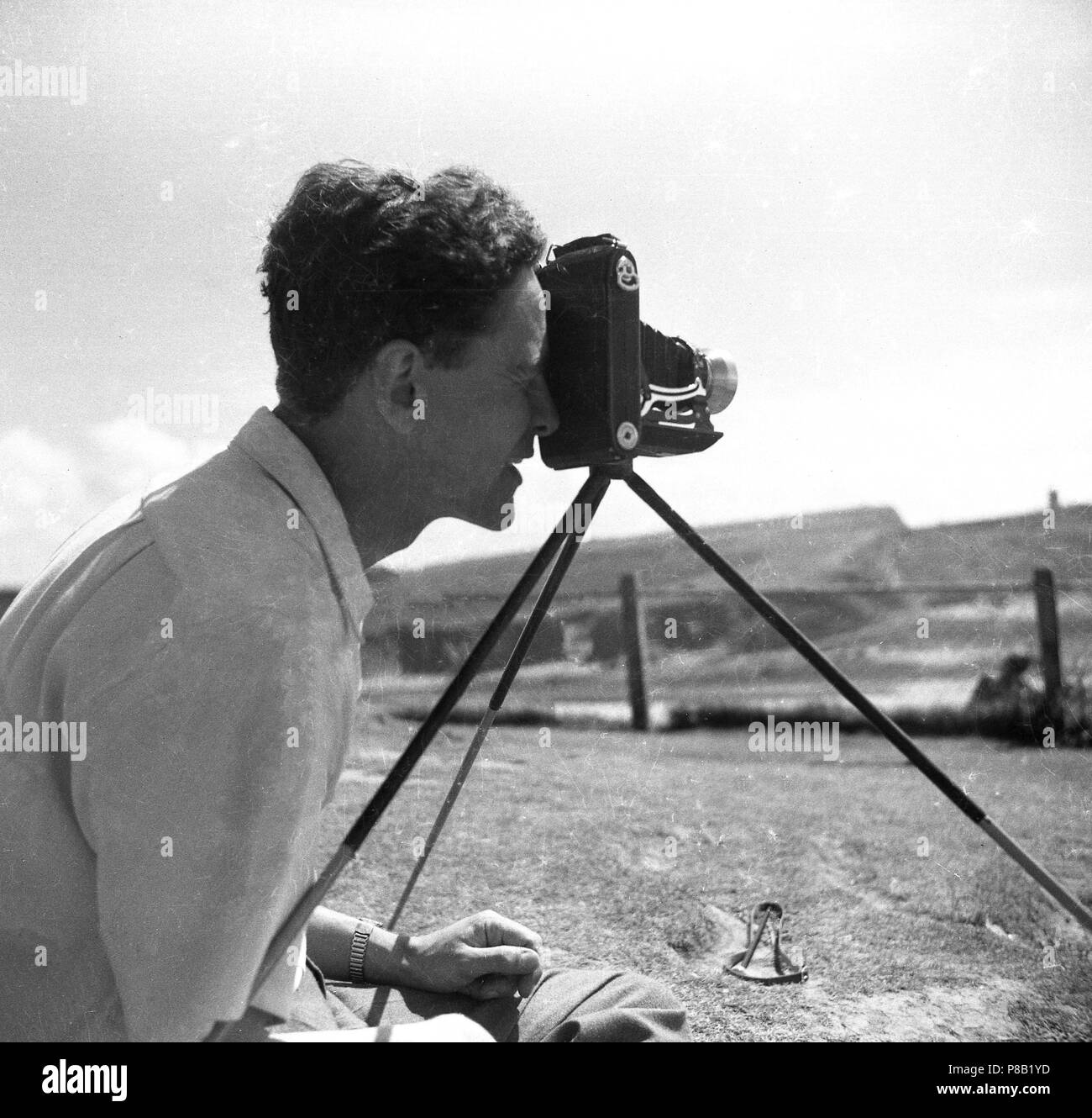 1950s, historical, man taking a photograph outside with a folding