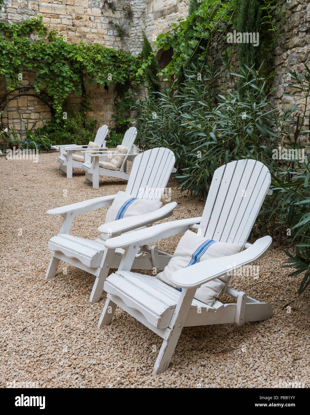 Painted white deckchairs in gravel courtyard of 18th century olive mill conversion - Stock Image