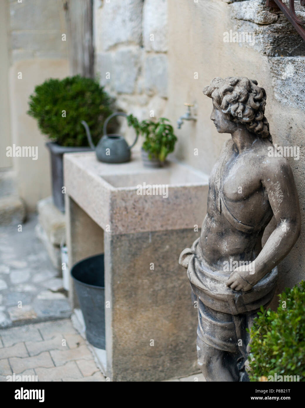 Classical statue and garden sink in curtyard of 18th century olive mill conversion - Stock Image