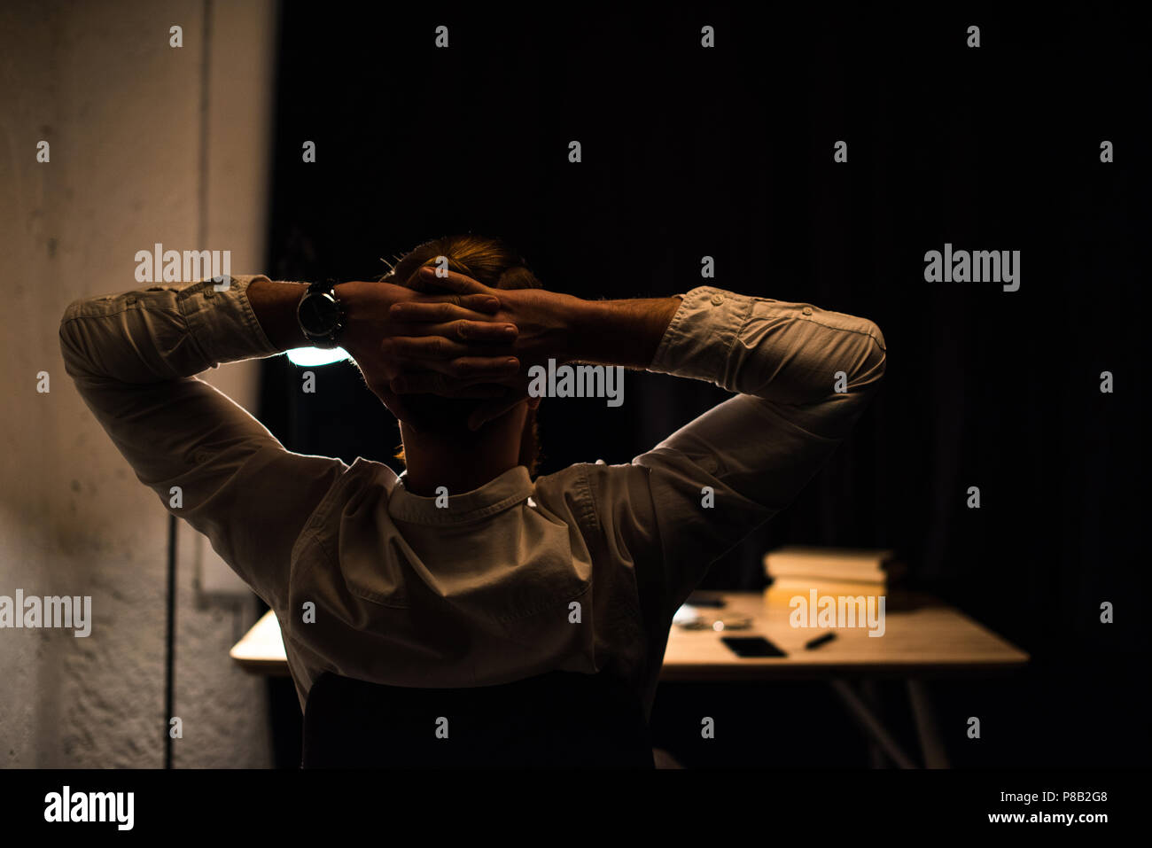 rear view of businessman sitting in office with hands behind head - Stock Image