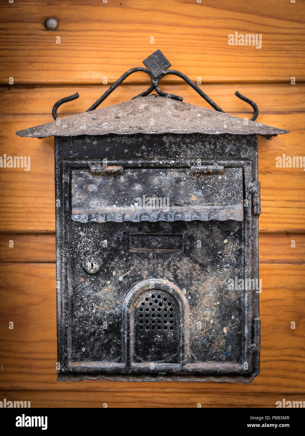 Old Weathered Mailbox Hanging On A Wooden Brown Door