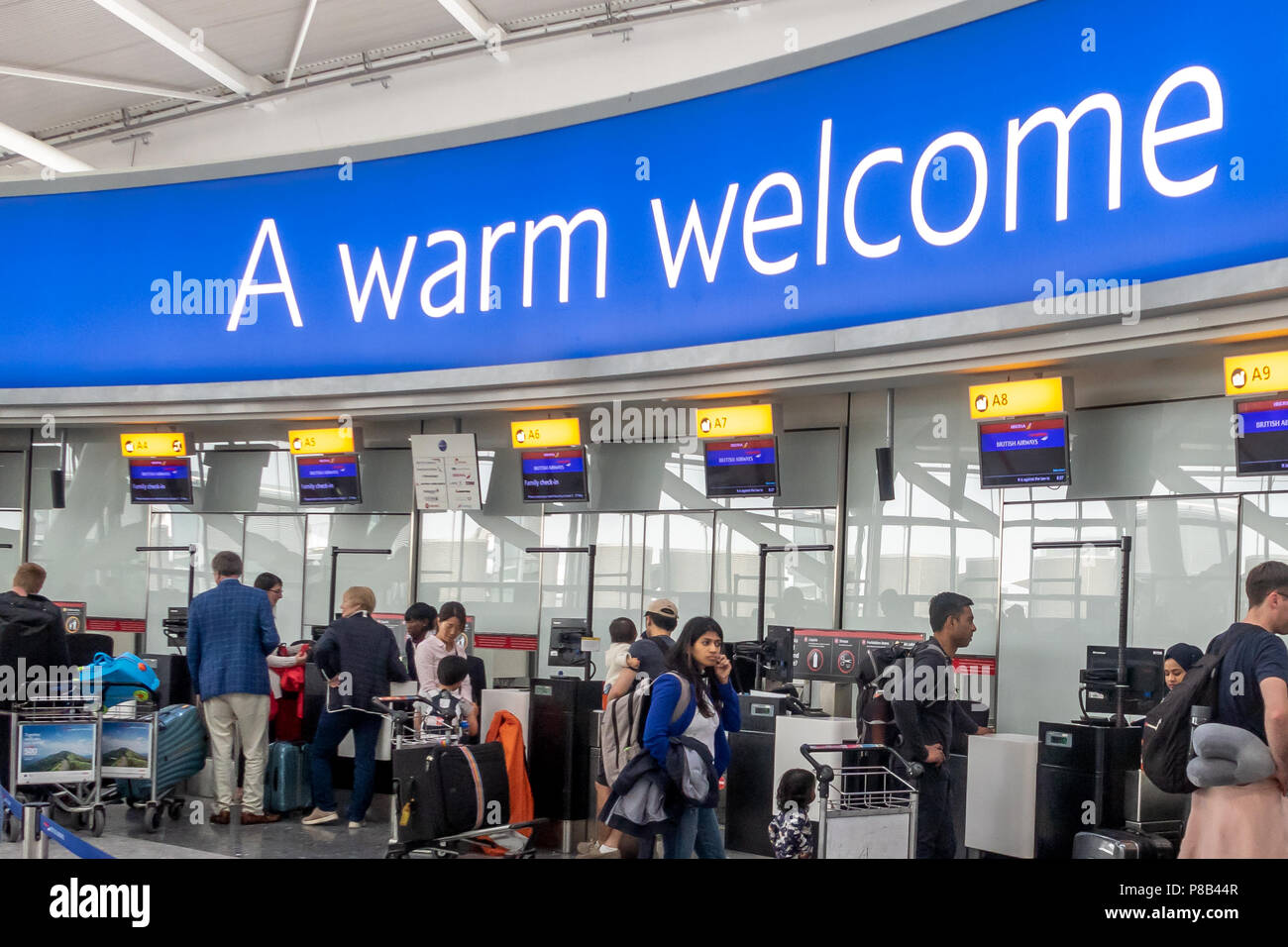 Passengers waiting at the British Airways check in desks at Heathrow Airport terminal 5 under a welcome sign - Stock Image