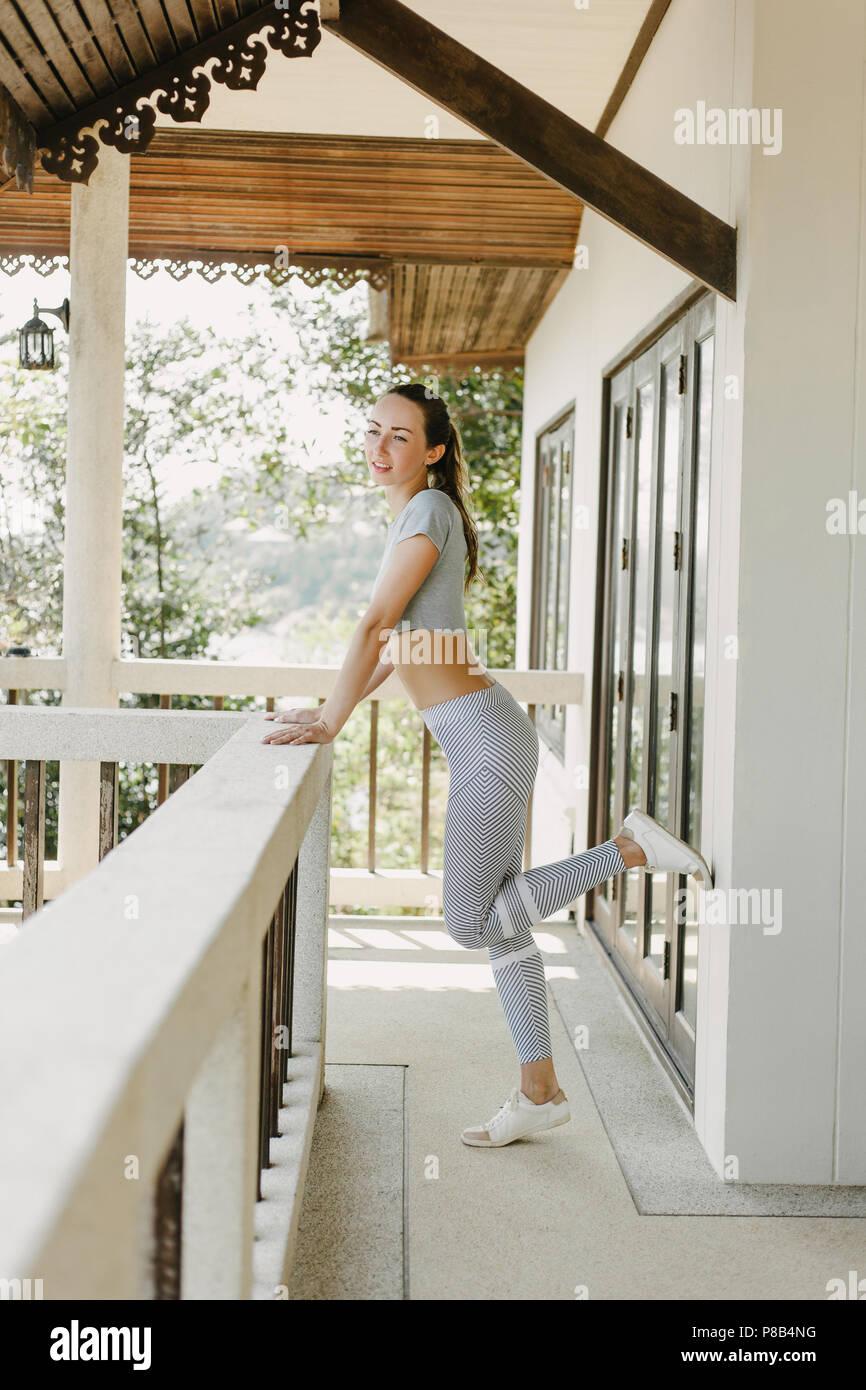 beautiful slim sportswoman in yoga pants posing on porch - Stock Image