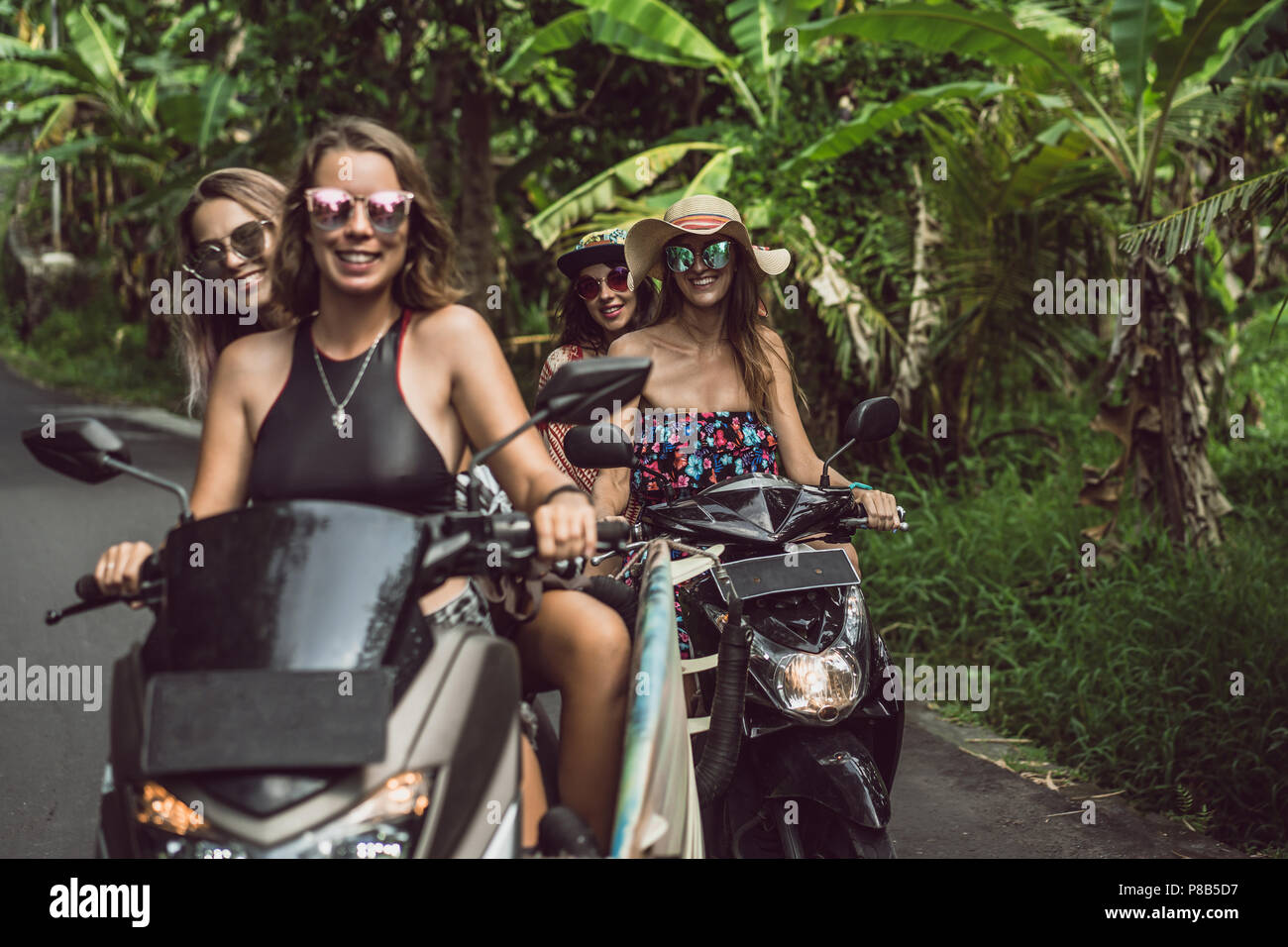 beautiful young women riding motorbikes and smiling at camera in jungles - Stock Image