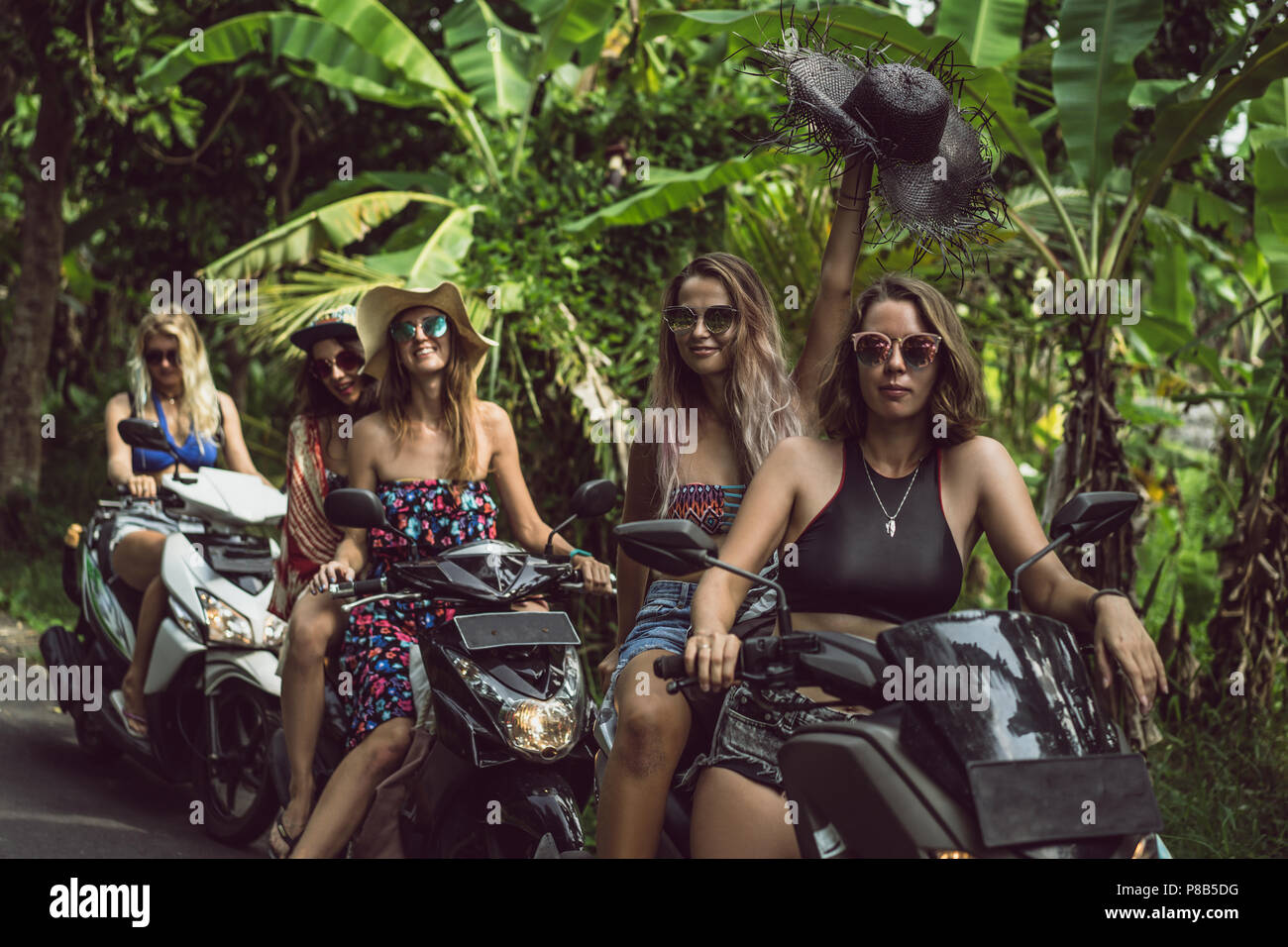 beautiful happy young women sitting on motorcycles in green jungles - Stock Image