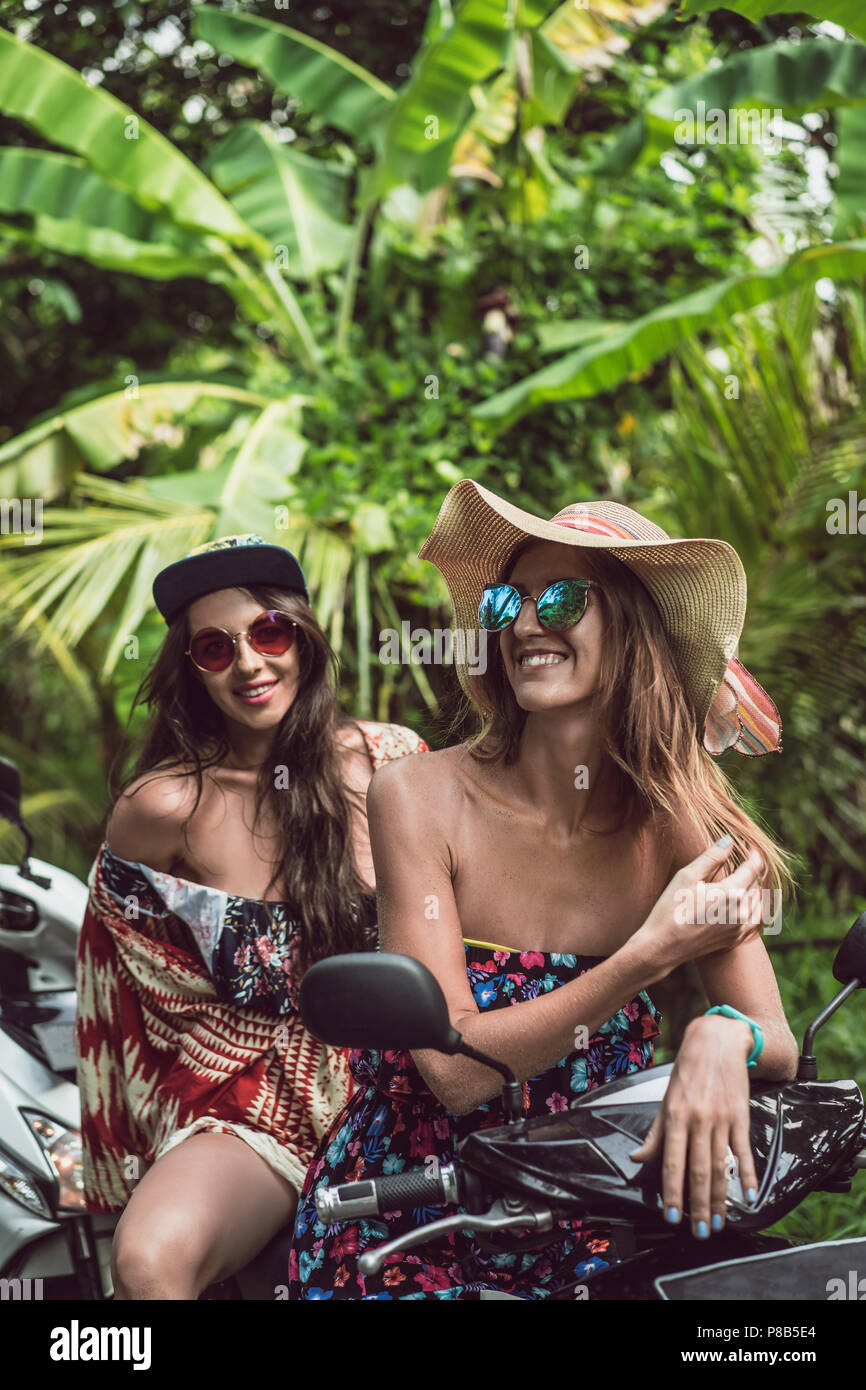beautiful young female friends in sunglasses sitting on motorcycle in jungles - Stock Image