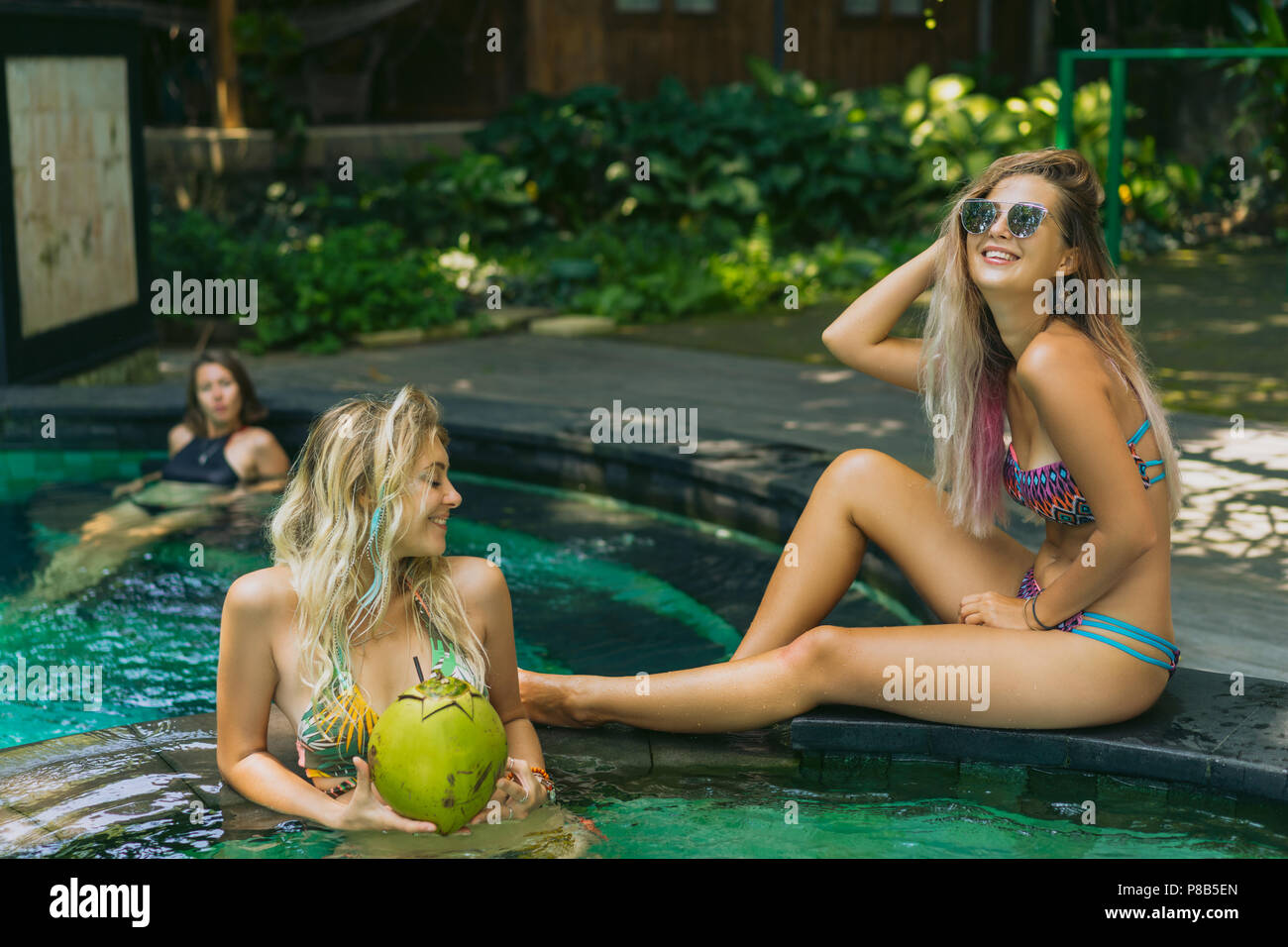 cheerful attractive young women in swimwear relaxing together at swimming pool - Stock Image
