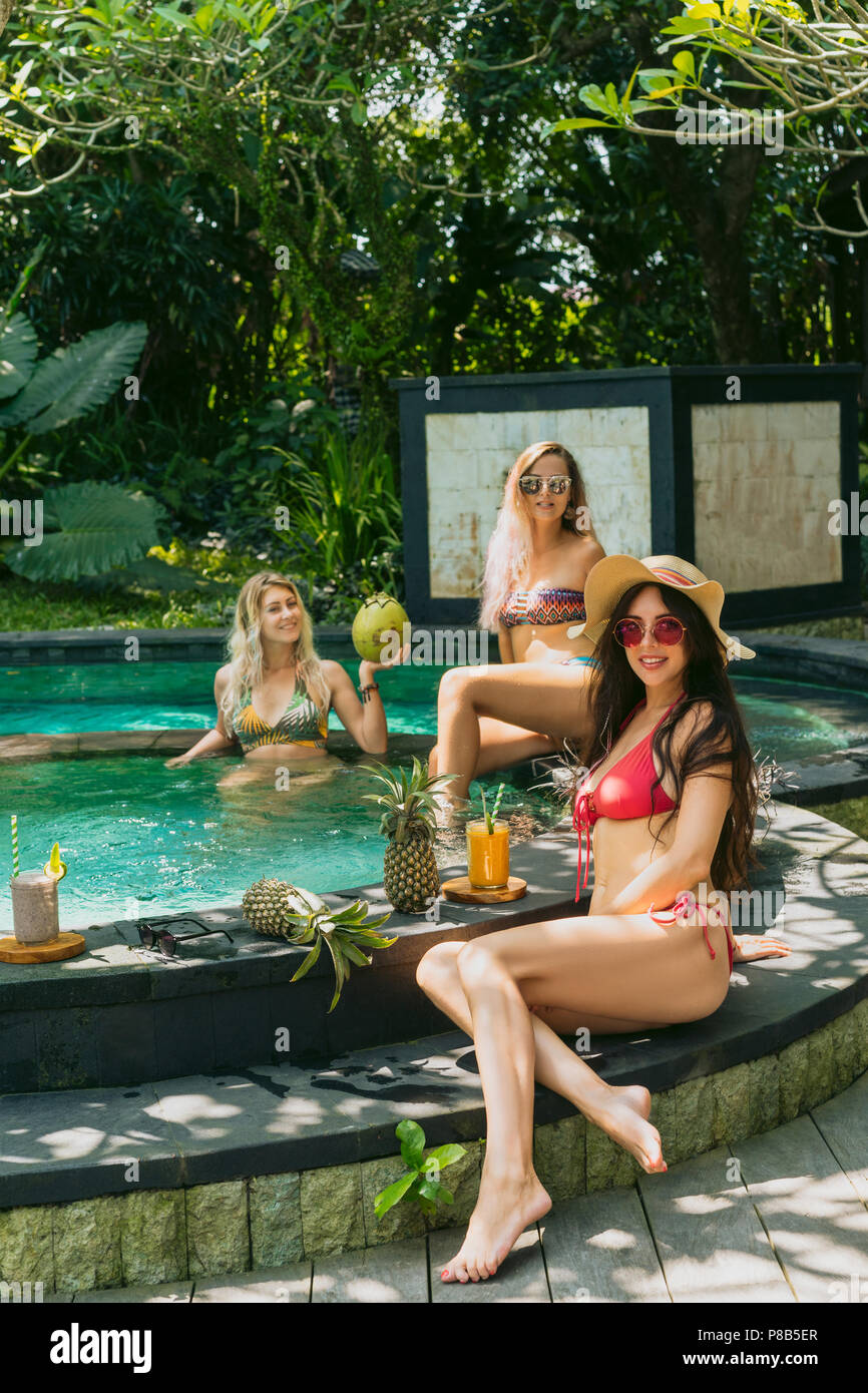 beautiful happy young women in swimwear resting together at swimming pool - Stock Image