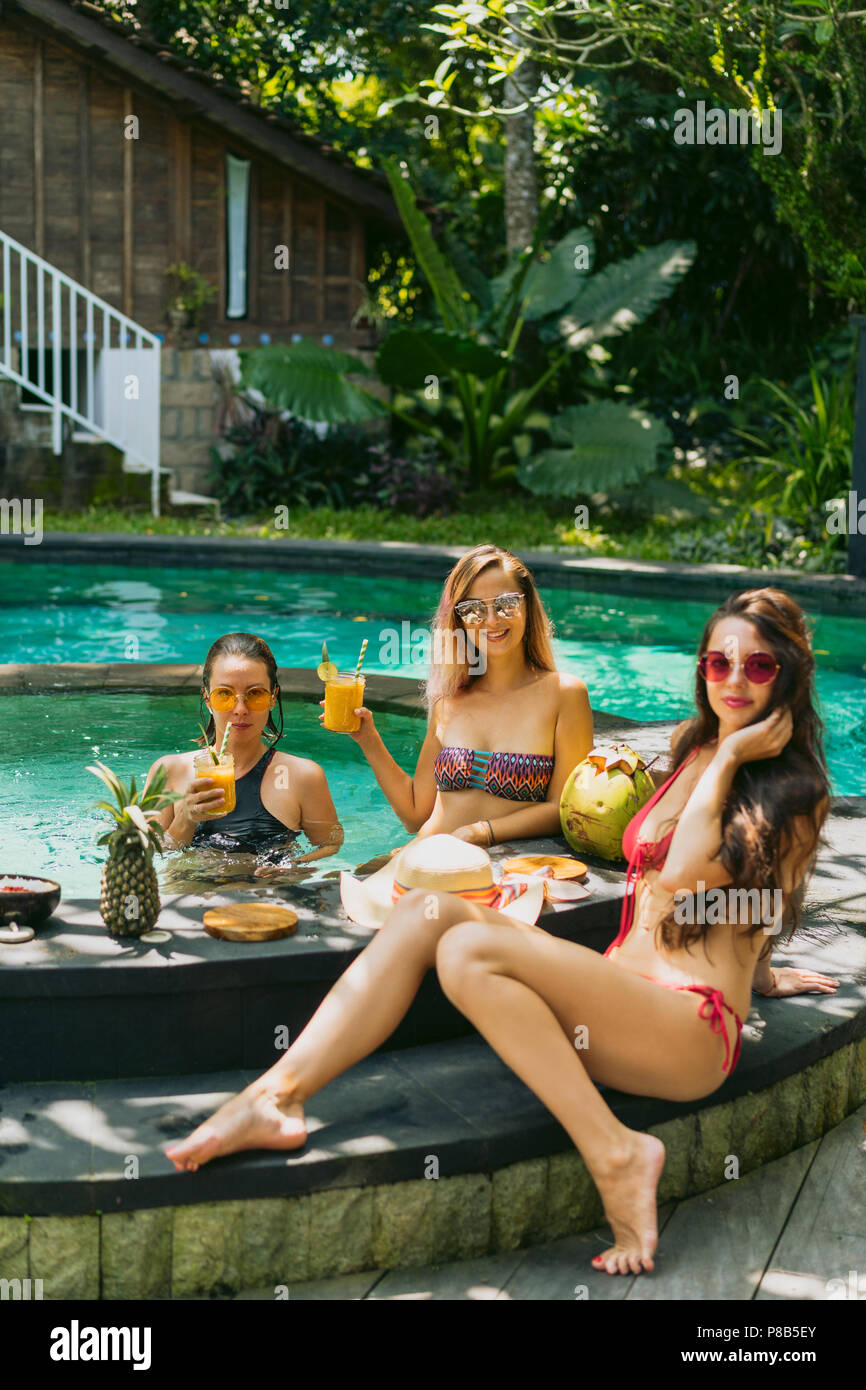 beautiful young women in swimwear looking at camera while drinking tropical cocktails at swimming pool - Stock Image