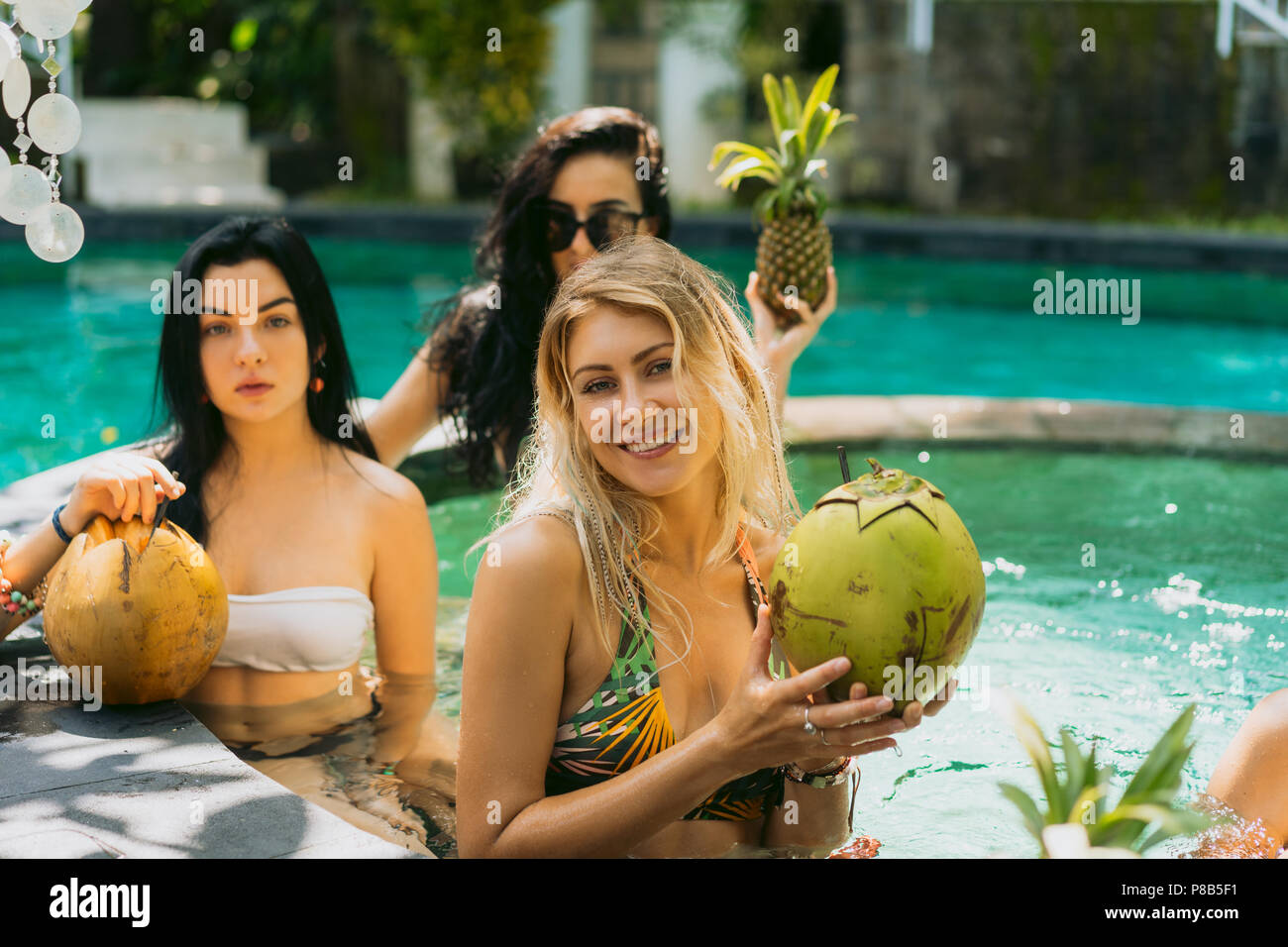beautiful young women in swimwear holding tropical fruits and cocktails at swimming pool - Stock Image