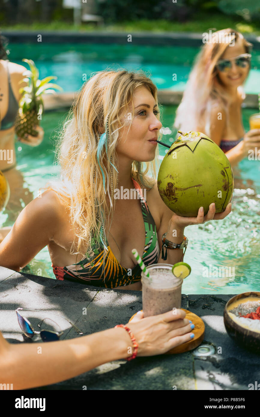 beautiful smiling young woman in bikini drinking cocktail from fresh coconut white relaxing in swimming pool - Stock Image