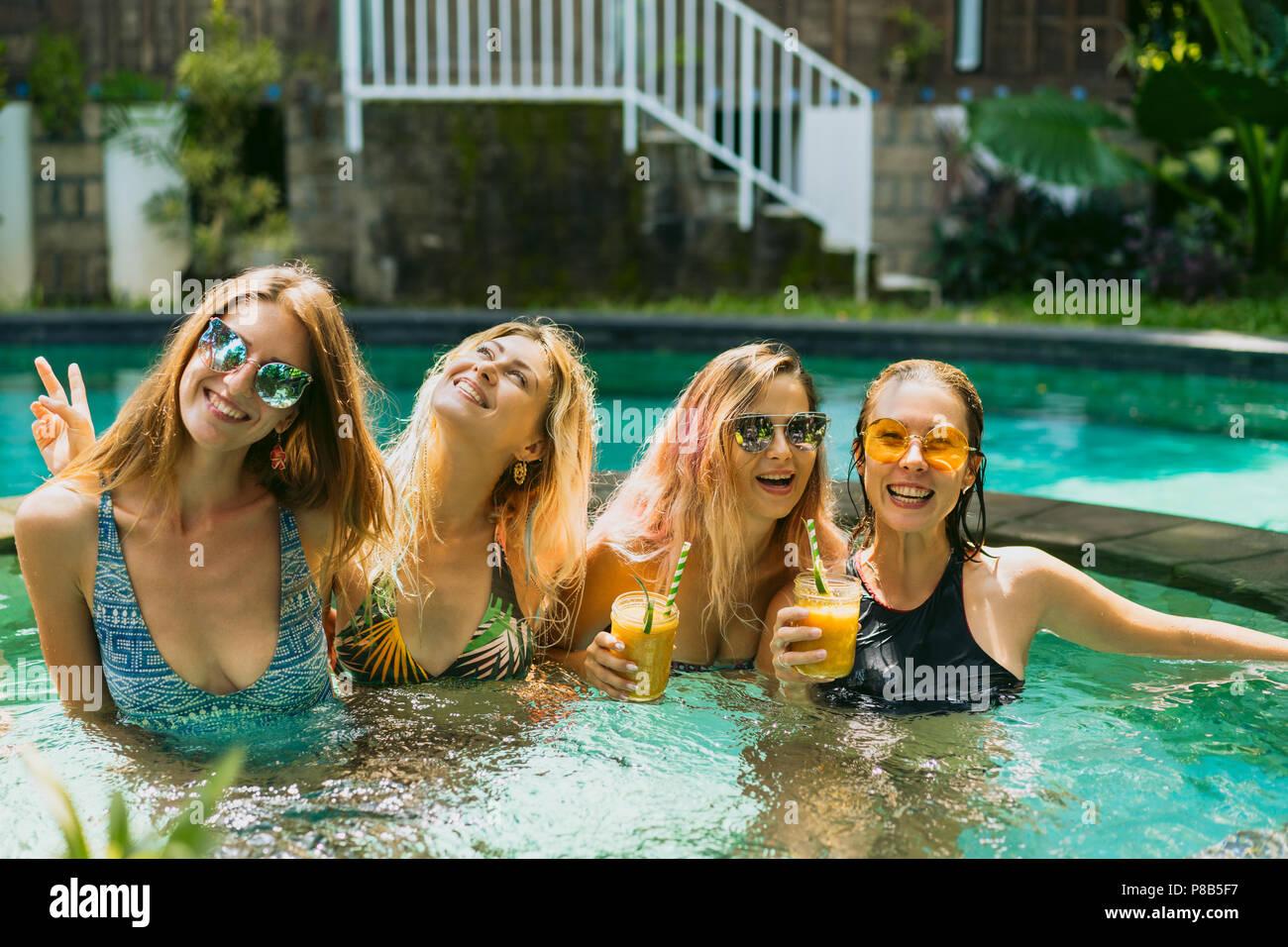 beautiful young women in swimwear having fun together at swimming pool - Stock Image