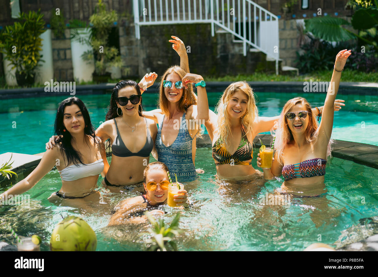beautiful young women in swimwear and sunglasses smiling at camera while having fun together at swimming pool - Stock Image
