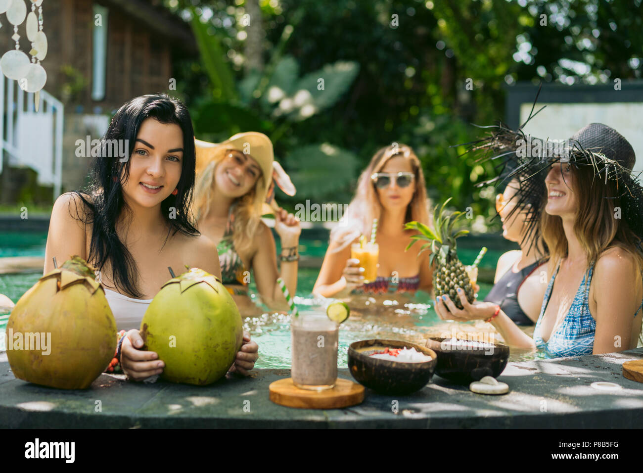 young women in swimwear drinking tropical cocktails and relaxing in swimming pool - Stock Image
