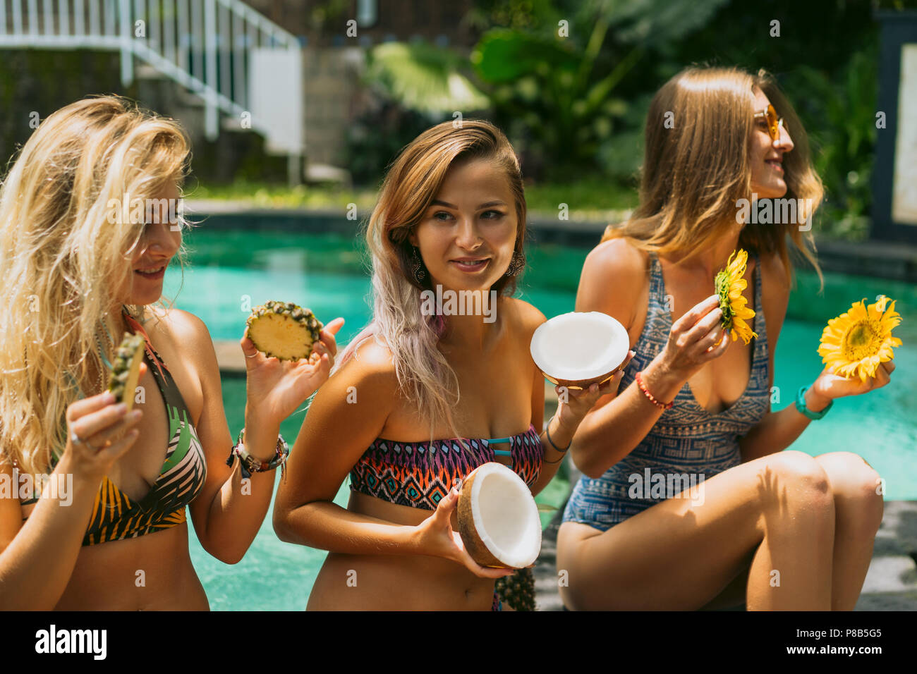 beautiful young women in swimwear holding sliced tropical fruits and flowers near swimming pool - Stock Image