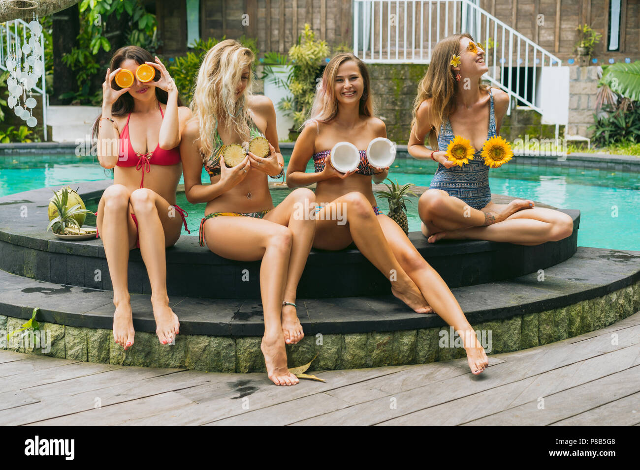 attractive girls in bikinis smiling and holding sliced tropical fruits near pool - Stock Image