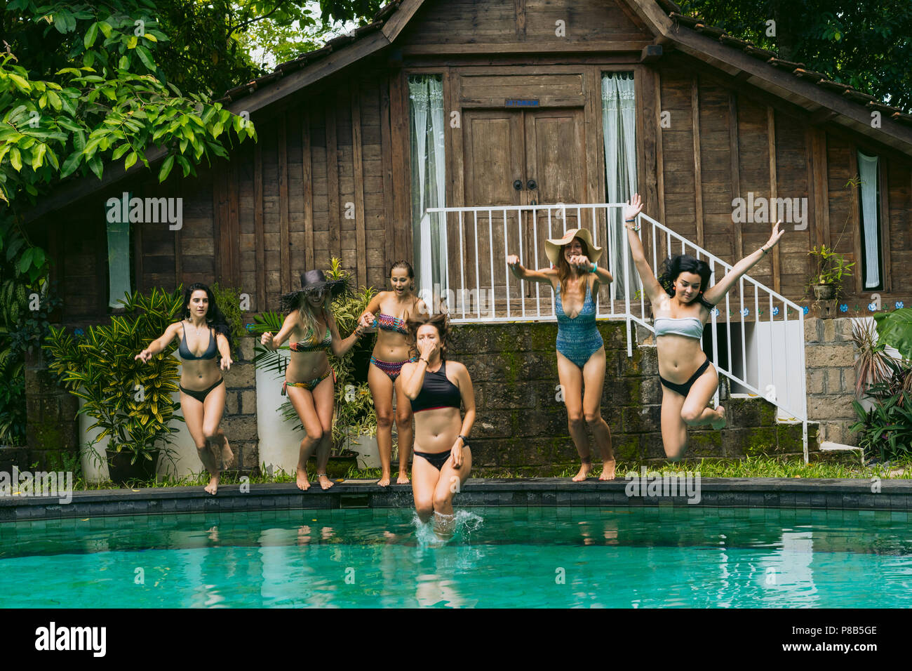 attractive young women in swimwear jumping in swimming pool at tropical resort - Stock Image