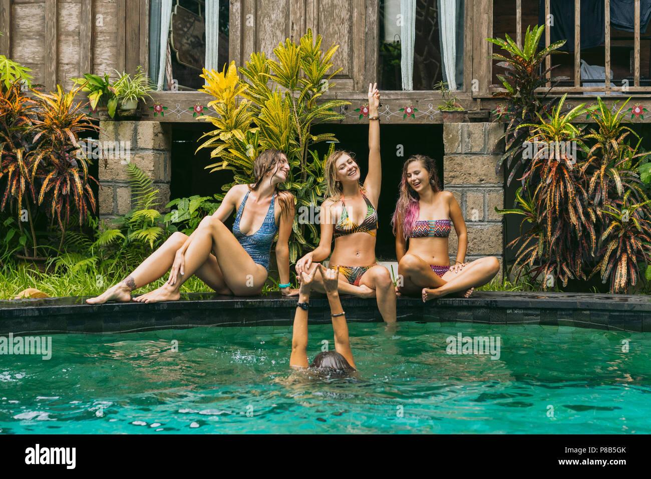 happy young women in swimwear having fun near swimming pool - Stock Image