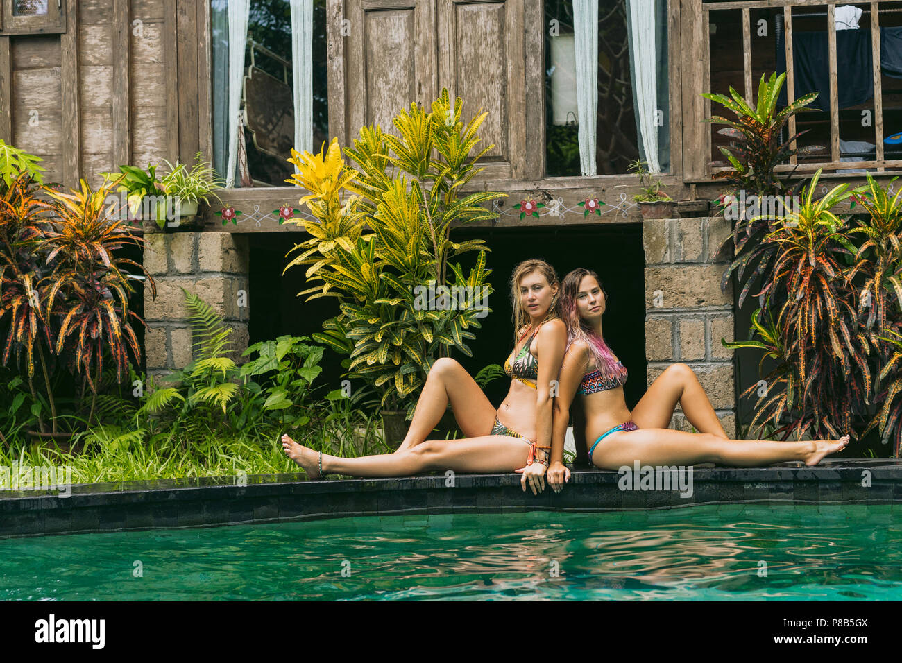 beautiful young women in swimwear resting near swimming pool and looking at camera - Stock Image