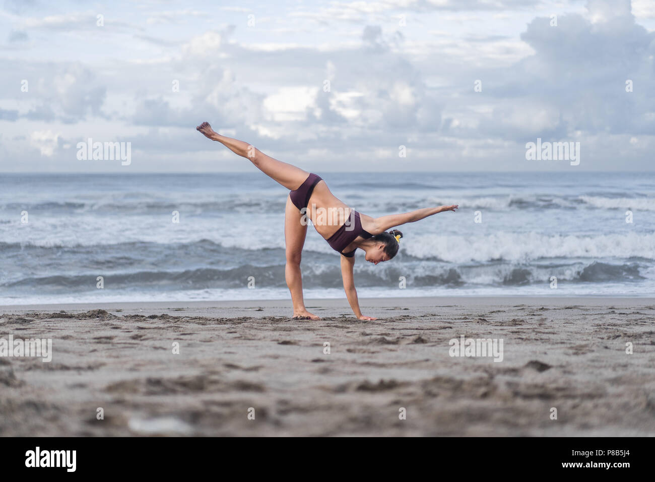 side view of fit young woman practicing yoga in Half Moon pose (Ardha Chandrasana) on seashore - Stock Image